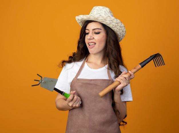 Geërgerd jonge vrouwelijke tuinman in uniform dragen tuinieren hoed houdt hark en kijkt naar schoffelhark geïsoleerd op oranje muur met kopie ruimte