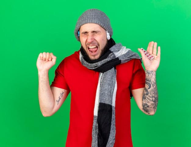 Geërgerd jonge zieke man dragen en houden van verpakkingen van medische pillen onder winter hoed en het dragen van sjaal houdt vuist en houdt pakje medische pillen geïsoleerd op groene muur