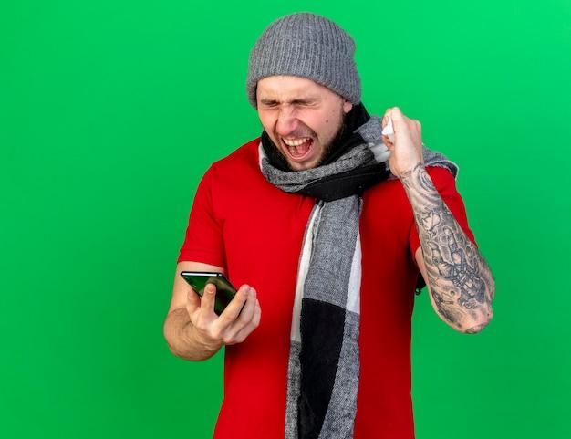Geërgerd jonge zieke man met winter muts en sjaal houdt vuist met weefsel en houdt telefoon geïsoleerd op groene muur