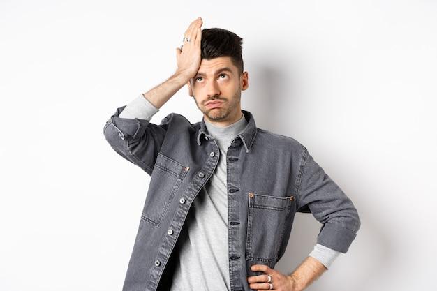 Geërgerd jongeman die er moe of gehinderd uitziet, rolt met zijn ogen en klapt op zijn voorhoofd, maakt facepalm van iets stoms, staande op een witte achtergrond.