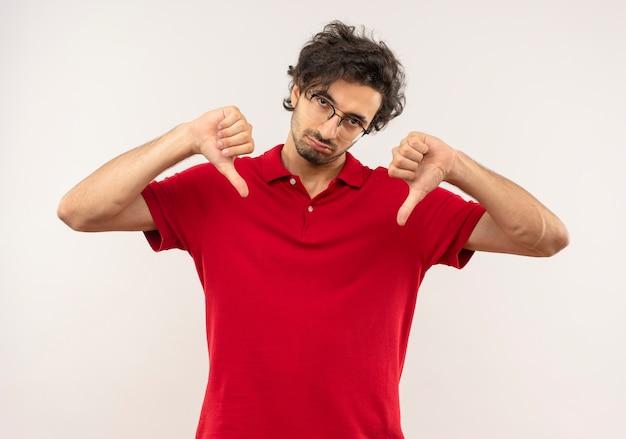 Geërgerd jongeman in rood shirt met optische bril duimen omlaag met twee handen geïsoleerd op een witte muur