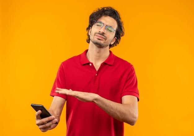 Geërgerd jongeman in rood shirt met optische bril houdt en wijst naar telefoon met gesloten ogen geïsoleerd op oranje muur