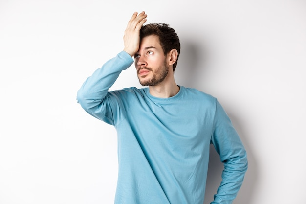 Geërgerd jongeman met baard, rologen en facepalm maken, pissig met iets, staande geïrriteerd op witte achtergrond