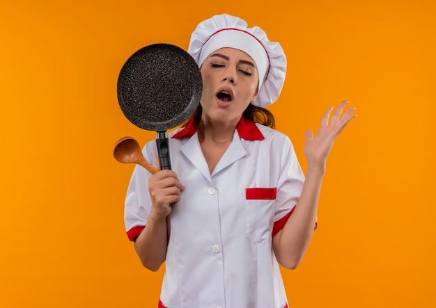 Geërgerd kaukasisch kokmeisje in uniform chef-kok houdt koekenpan en houten lepel met gesloten ogen geïsoleerd op een oranje achtergrond met kopie ruimte