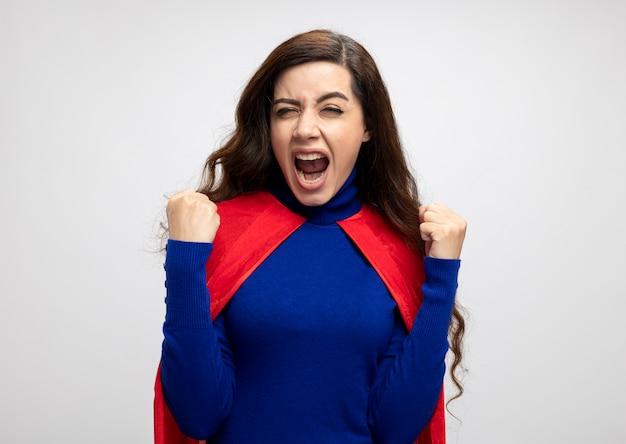 Geërgerd kaukasisch superheld meisje met rode cape houdt vuisten op wit
