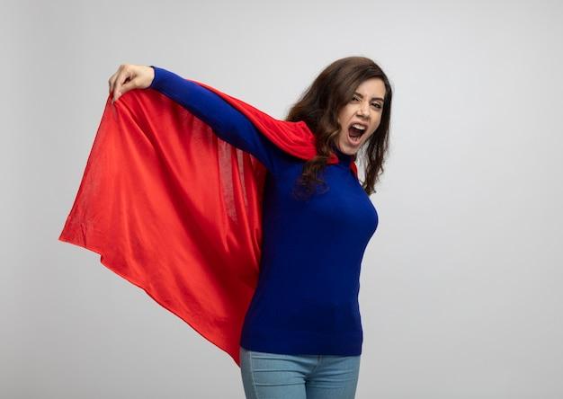 Geërgerd kaukasisch superheldmeisje houdt rode cape geïsoleerd op een witte muur met kopie ruimte