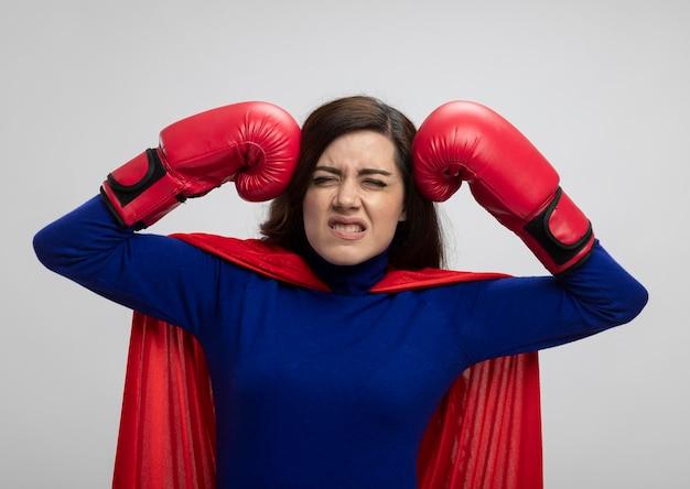Geërgerd kaukasisch superheldmeisje met rode cape die het dragen van bokshandschoenen dragen die vuisten op hoofd zetten