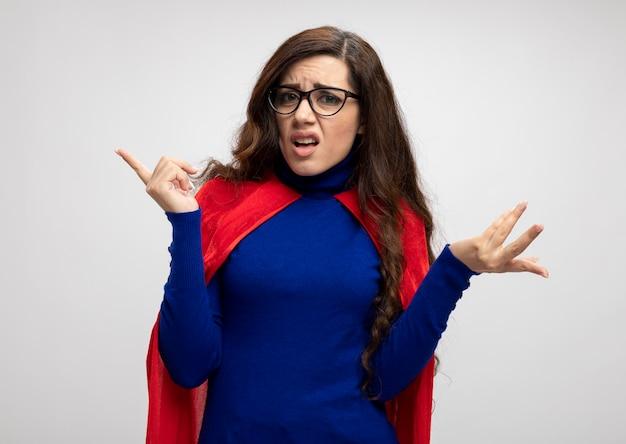 Geërgerd kaukasisch superheldmeisje met rode cape in optische glazen staat met opgeheven hand