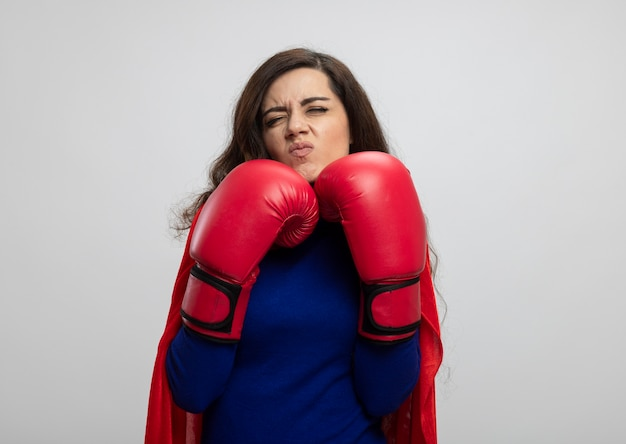 Geërgerd kaukasisch superheromeisje met rode cape die het dragen van bokshandschoenen dragen die zich in rek bevinden dat op witte muur met exemplaarruimte wordt geïsoleerd