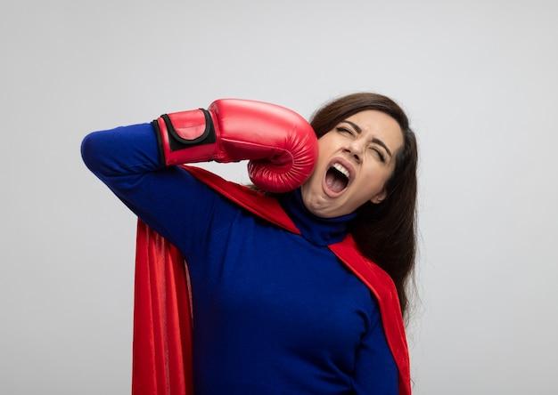 Geërgerd kaukasisch superheromeisje met rode cape die het dragen van bokshandschoenen