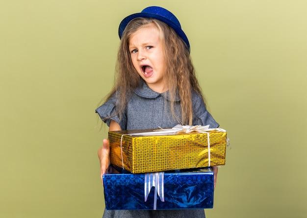 Geërgerd klein blond meisje met blauwe feestmuts met geschenkdozen geïsoleerd op olijfgroene muur met kopie ruimte