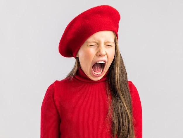 Geërgerd klein blond meisje met een rode baret die de ogen gesloten houdt en schreeuwt geïsoleerd op een witte muur