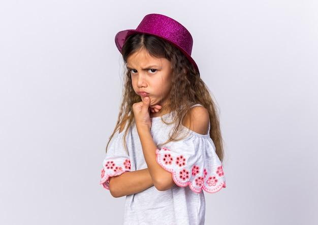 Geërgerd klein kaukasisch meisje met paarse feestmuts met haar kin geïsoleerd op een witte muur met kopie ruimte