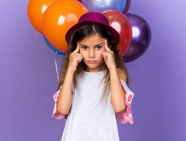Geërgerd klein kaukasisch meisje met violet feestmuts dat wenkbrauwen trekt met vingers die voor heliumballonnen staan geïsoleerd op paarse muur met kopieerruimte