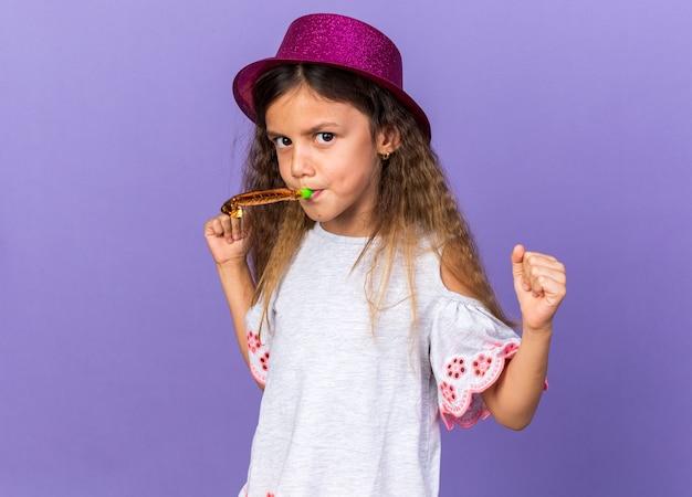 Geërgerd klein kaukasisch meisje met violette feestmuts blaast partij fluitje en vuisten omhoog geïsoleerd op paarse muur met kopie ruimte te houden