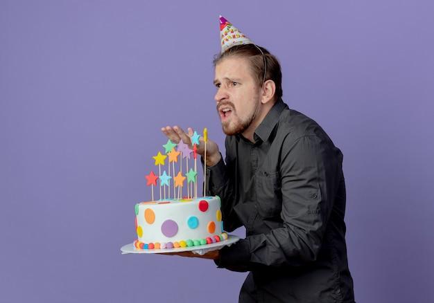 Geërgerd knappe man in verjaardag pet staat zijwaarts houdt cake naar voren geïsoleerd op paarse muur