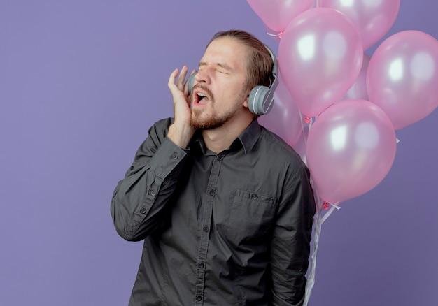 Geërgerd knappe man op koptelefoon staat met helium ballonnen geïsoleerd op paarse muur