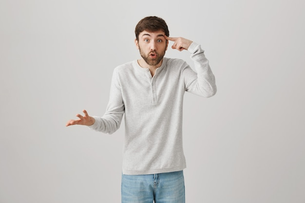 Geërgerd man die zijn vinger over de tempel rolt en stom gedrag uitscheldt