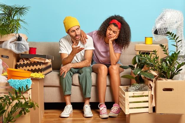 Geërgerd man gebaart boos, zit in de buurt van een donkere vriendin, verhuist naar een nieuw appartement, moe van het uitpakken van kartonnen dozen, poseert in de woonkamer tegen de blauwe muur, gaat een nieuw huis binnen. vastgoed