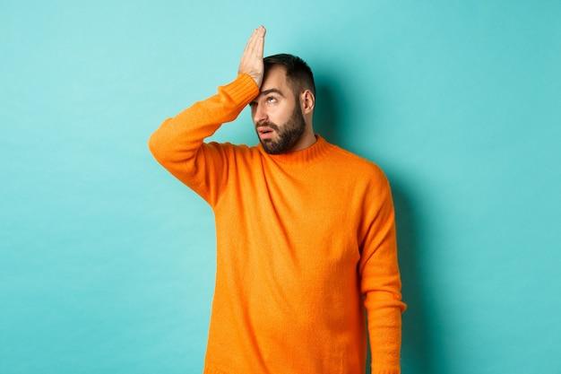 Geërgerd man rolt ogen en maakt facepalm, staande over turkooizen achtergrond.