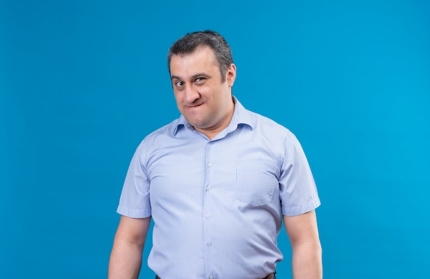 Geërgerd man van middelbare leeftijd in blauw shirt kijken naar de camera met een ontevreden uitdrukking op een blauwe ruimte