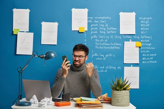 Geërgerd mannelijke baas werkt thuis in gezellige werkplek, organiseert werkproces, balken vuist en tanden met irritatie