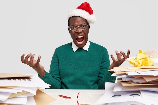 Geërgerd mannetje spreidt zijn handpalmen, voelt zich geïrriteerd terwijl hij werkt tijdens vakanties, moet veel papieren analyseren, draagt hoofddeksel van de kerstman, groene trui