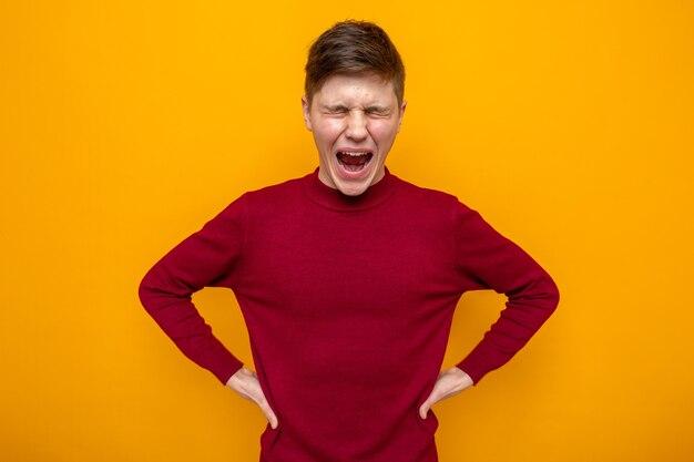 Geërgerd met gesloten ogen die handen op een hippe jonge knappe kerel zetten die een rode trui draagt die op een oranje muur is geïsoleerd