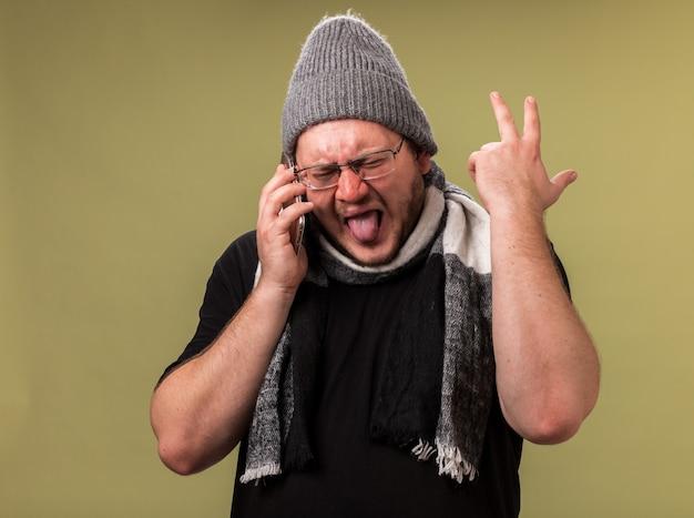 Geërgerd met gesloten ogen, een zieke man van middelbare leeftijd die een wintermuts en sjaal draagt, spreekt op de telefoon terwijl hij zijn hand opsteekt