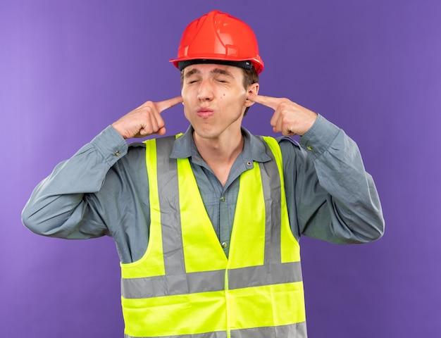 Geërgerd met gesloten ogen jonge bouwer man in uniform gesloten oren geïsoleerd op blauwe muur
