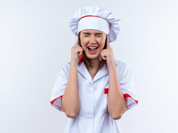 Geërgerd met gesloten ogen jonge vrouwelijke kok met chef-kok uniform bedekt oren geïsoleerd op een witte achtergrond