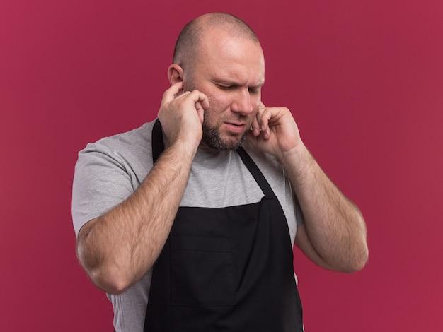 Geërgerd met gesloten ogen slavische mannelijke kapper van middelbare leeftijd in uniforme gesloten oren geïsoleerd op roze muur