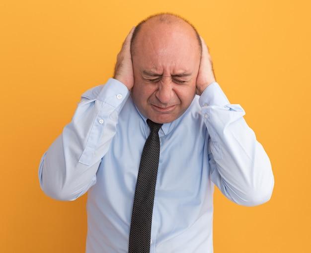 Geërgerd met verlaagd hoofd man van middelbare leeftijd met een wit t-shirt met stropdas bedekt oren geïsoleerd op een oranje muur