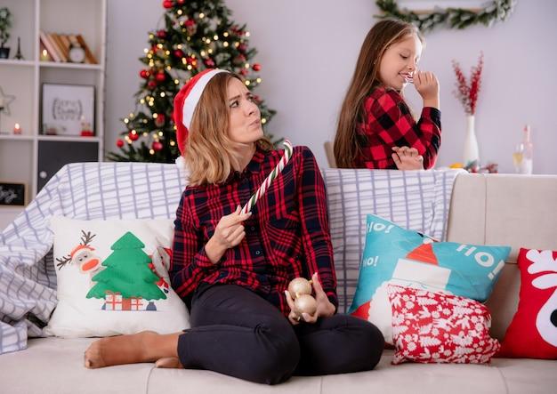 Geërgerd moeder met kerstmuts houdt een deel van gebroken riet van het suikergoed zittend op de bank en kijkt naar tevreden dochter eten riet van het suikergoed thuis genieten van de kersttijd
