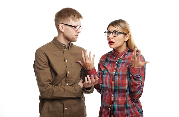 Geërgerd mooi meisje in kattenbril en geruit overhemd gebaart met beide handen, haar verontwaardiging uitend terwijl ze boos was op haar onwetende vriend die hun jubileum weer vergat