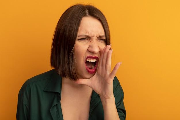 Geërgerd mooie blanke vrouw houdt de hand dicht bij de mond en doet alsof ze iemand belt die naar de zijkant op oranje kijkt