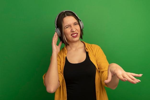 Geërgerd mooie blanke vrouw op koptelefoon houdt hand open geïsoleerd