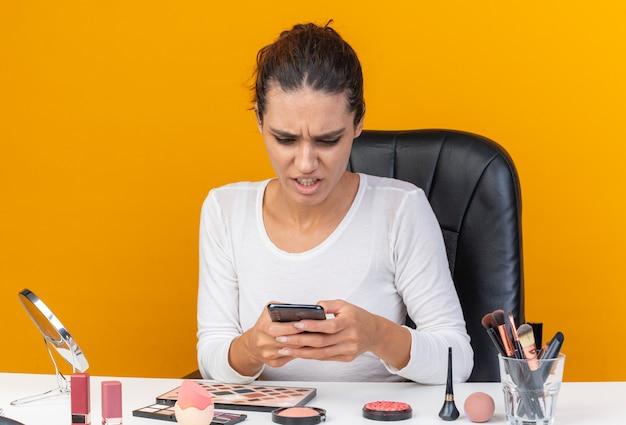 Geërgerd mooie blanke vrouw zittend aan tafel met make-up tools houden en kijken naar telefoon geïsoleerd op oranje muur met kopieerruimte