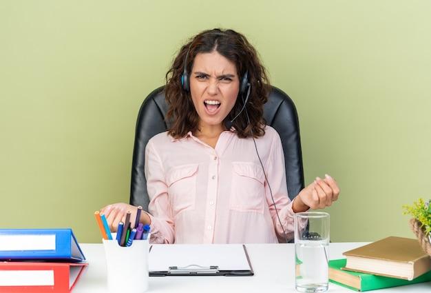 Geërgerd mooie blanke vrouwelijke callcenter-operator op koptelefoon zittend aan bureau met kantoorhulpmiddelen die handen open houden geïsoleerd op groene muur