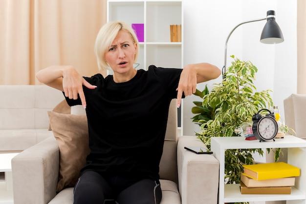 Geërgerd mooie blonde russische vrouw zit op fauteuil naar beneden met twee handen in de woonkamer