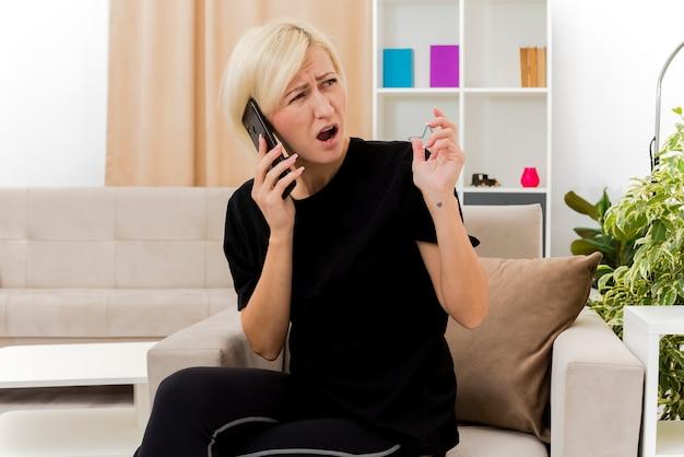 Geërgerd mooie blonde russische vrouw zit op fauteuil praten over telefoon kant kijken