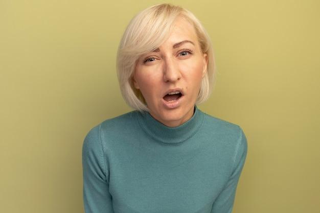 Geërgerd mooie blonde slavische vrouw kijkt naar voorzijde geïsoleerd op olijfgroene muur