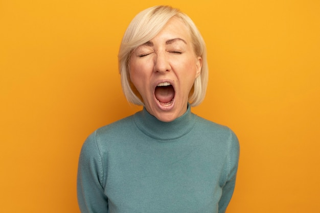 Geërgerd mooie blonde slavische vrouw staat met gesloten ogen schreeuwen tegen iemand geïsoleerd op oranje muur