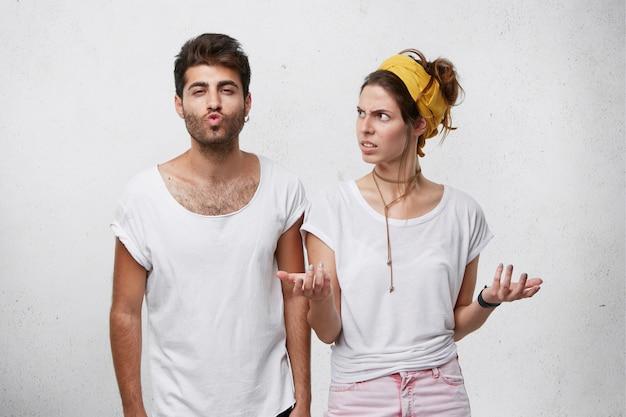 Geërgerd mooie vrouw gebaart en staart boos naar haar ontrouwe knappe vriend die zelfvoldane uitdrukking heeft, lippen pruilend alsof ze een kus blaast, flirt met iemand