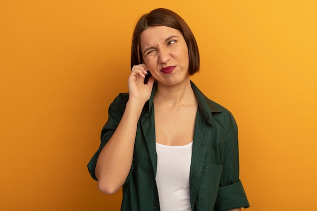 Geërgerd mooie vrouw sluit oor met vinger geïsoleerd op oranje muur
