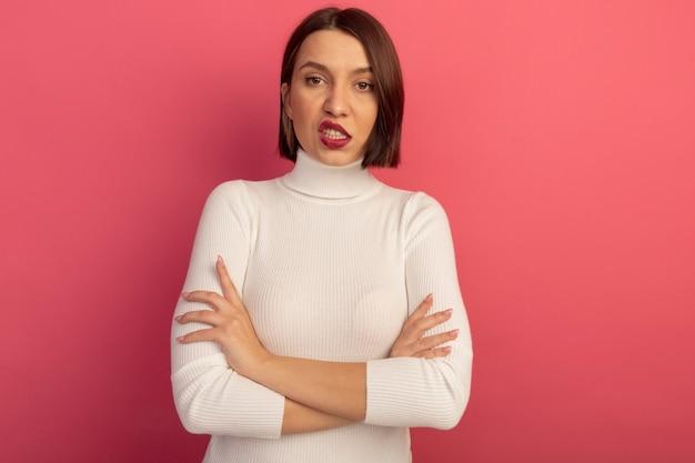 Geërgerd mooie vrouw stond met gekruiste armen geïsoleerd op roze muur