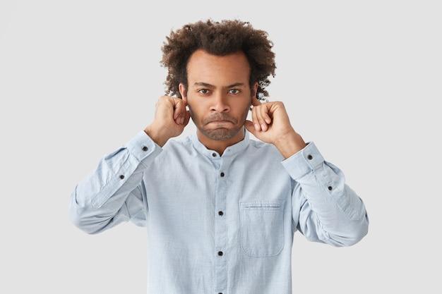 Geërgerd, ontevreden man, student drukt zijn lippen op elkaar en bedekt zijn oren