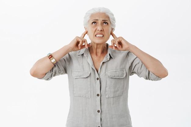 Geërgerd, ontevreden oude vrouw die luide buren klaagt, opkijkt en oren met vingers sluit