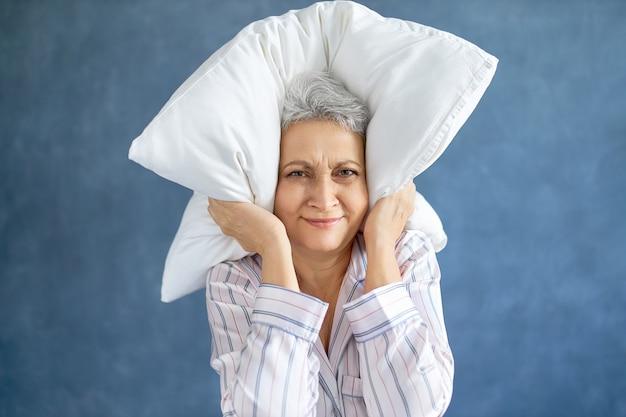 Geërgerd ontevreden volwassen vrouw met grijze haren grimassen slapeloze nacht vanwege luide muziek