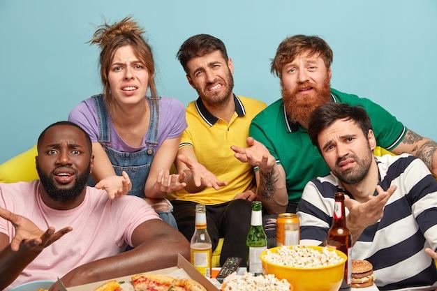 Geërgerd ontevreden vrienden geïrriteerd door te veel televisiereclame, gebaren van apathie, ontevreden verontwaardigde gezichtsuitdrukkingen, eten pizza en popcorn. gezelschap, vrije tijd concept